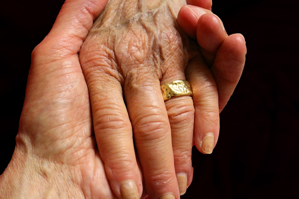 Picture of two hands, one with a gold ring on the ring finger.