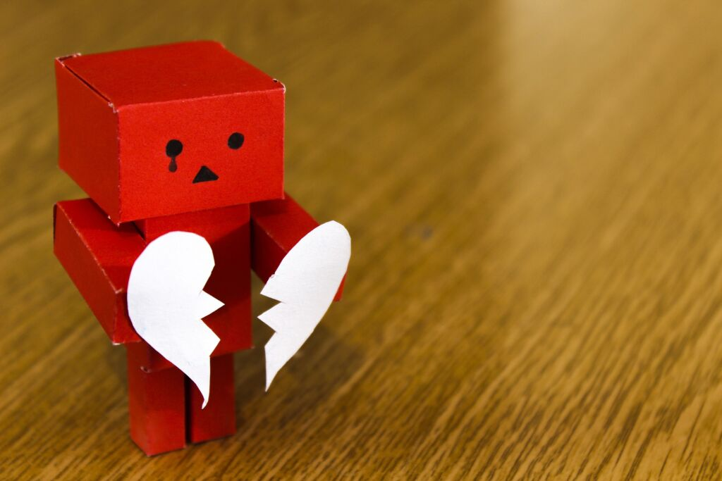 cardboard figure with part of a heart in each hand