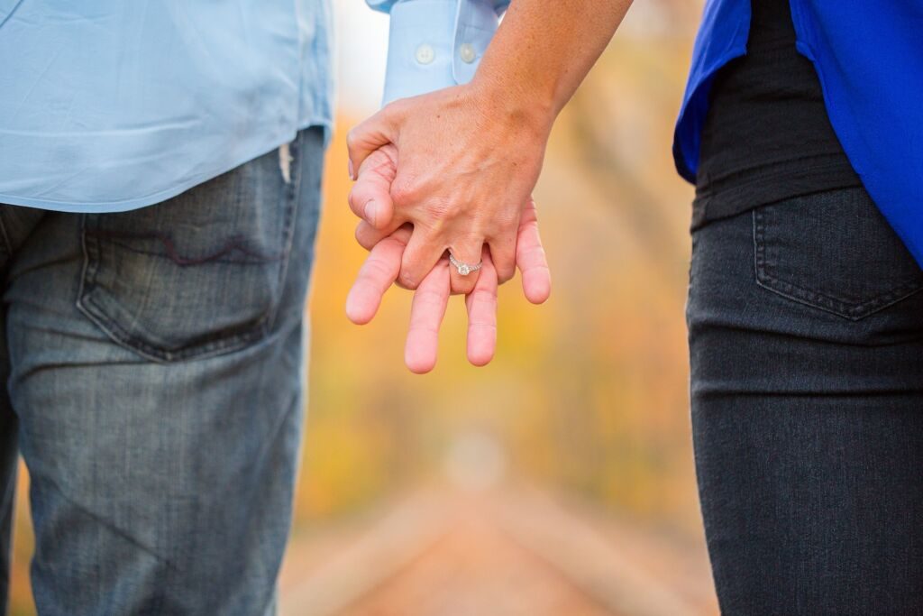 Photograph of two white people holding hands, background out of focus.
