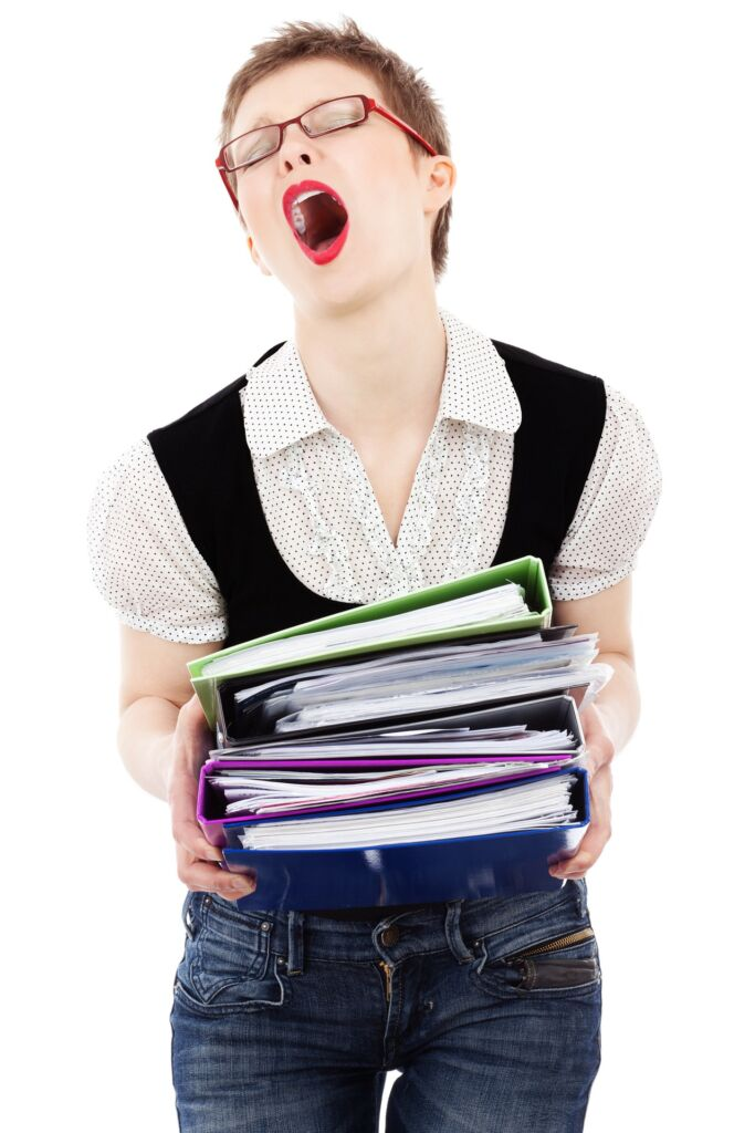 Woman yawning with eyes closed holding lots of folders.