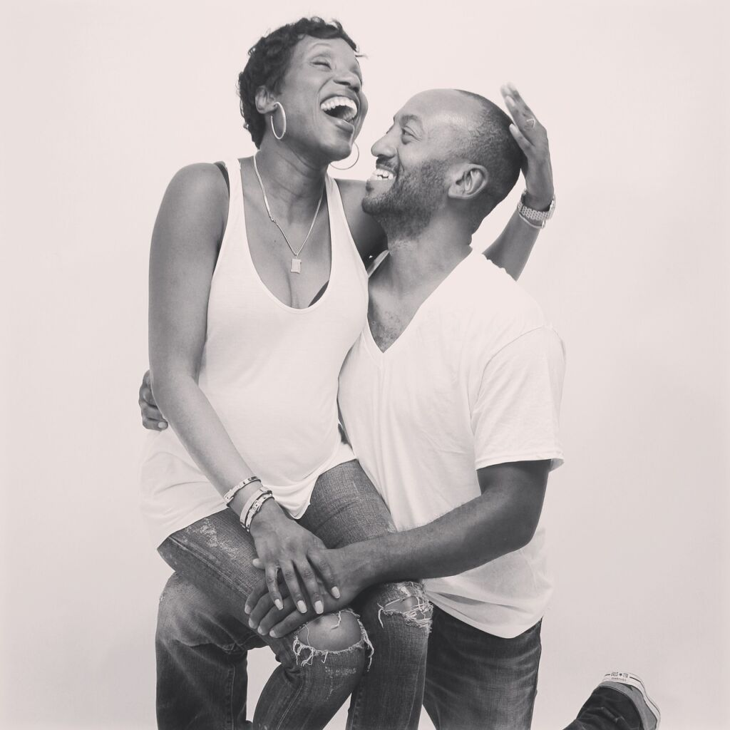 Black and white picture of a black woman sitting on a black man's knee. Both of them look joyful.