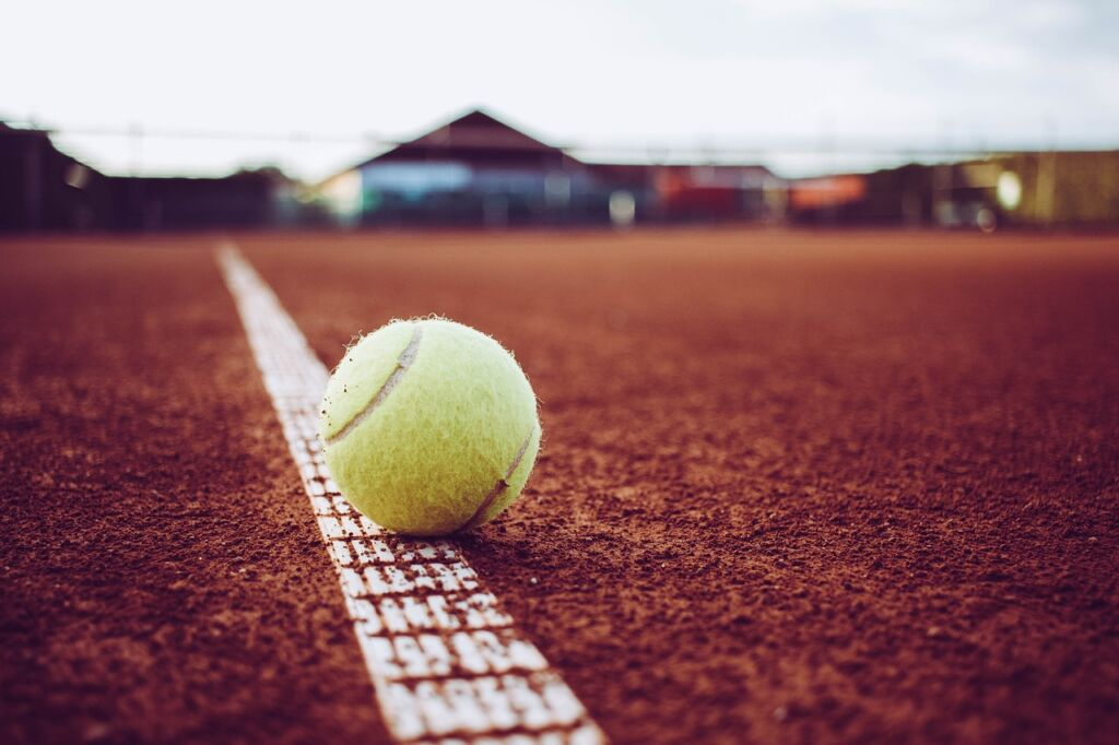Red clay tennis court with a yellow tennis ball on the white boundary line.