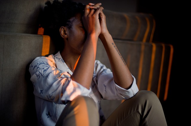 black person sitting on the floor holding clasped hands to their forehead. They appear sad/depressed.