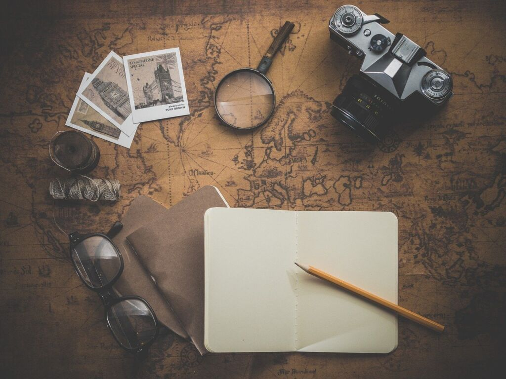 Brown world map in background with camera, glasses, string, photographs magnifying glass and book with pencil on top.