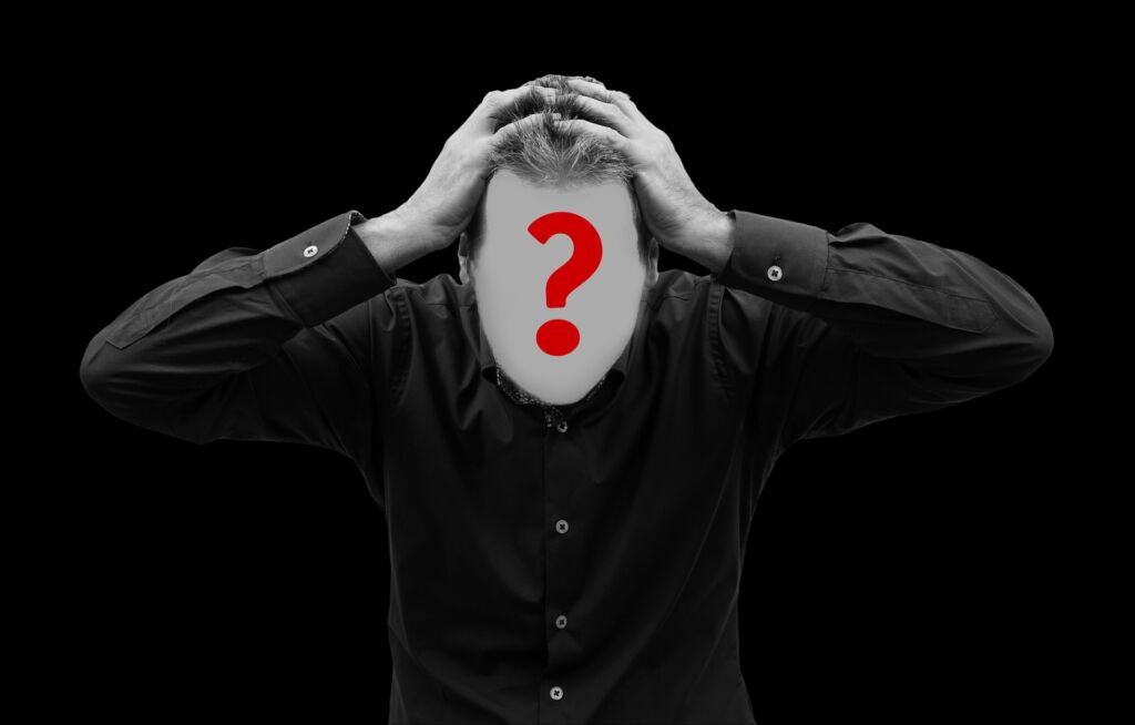 White man in black shirt on black background. His face is blurred out and has a red question mark over it.